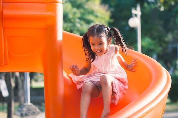 Nettes asiatisches kindermädchen, das spaß hat, schieber im spielplatz in der sommerzeit zu spielen