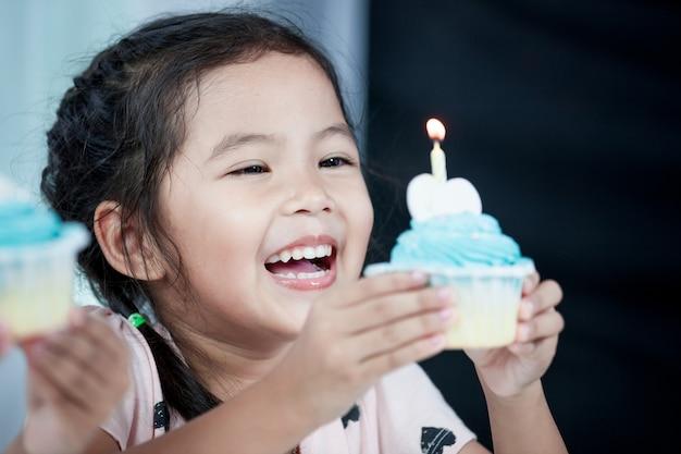 Nettes asiatisches kindermädchen, das spaß lächelt und hat, ihren geburtstagskleinen kuchen in der partei durchzubrennen