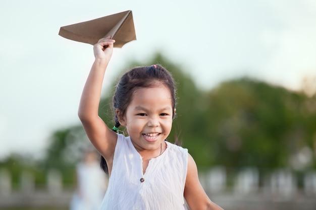 Nettes asiatisches kindermädchen, das spielzeugpapierflugzeug auf dem gebiet im weinlesefarbton läuft und spielt