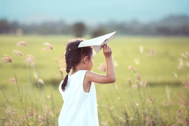 Nettes asiatisches kindermädchen, das spielzeugpapierflugzeug auf dem gebiet im weinlesefarbton spielt
