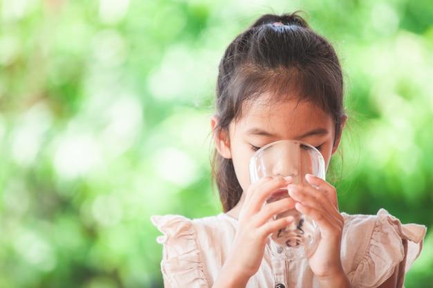 Nettes asiatisches kindermädchen, das süßwasser vom glas trinkt