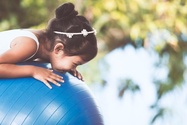 Nettes asiatisches kindermädchen, das übung auf eignungsball ausdehnend tut