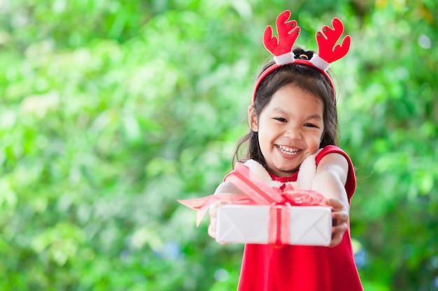 Nettes asiatisches kindermädchen, das weihnachtsgeschenk hält und gibt