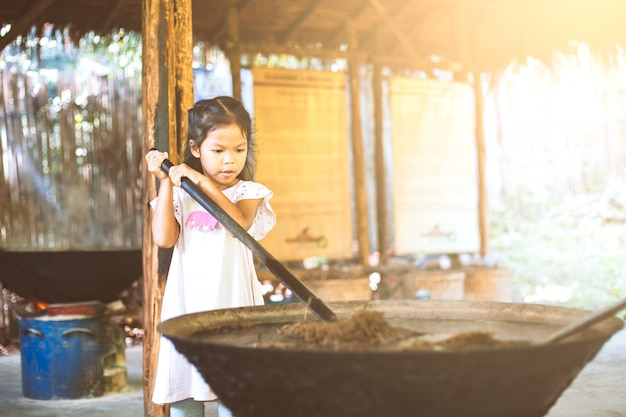 Nettes asiatisches kindermädchen, das wie man recyclingpapier vom poop von elefanten lernt, herstellt