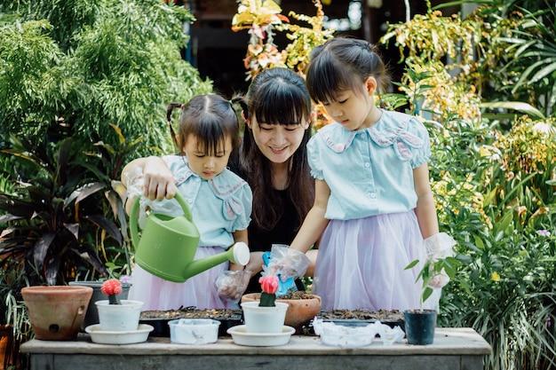 Nettes asiatisches kindermädchen hilft mutter beim pflanzen oder cutivieren der pflanzen im garten.