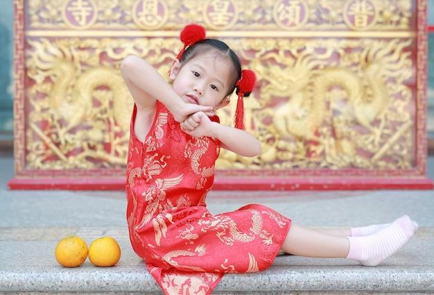 Nettes asiatisches kindermädchen im kleid des traditionellen chinesen mit gestenreverence