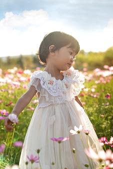 Nettes asiatisches kindermädchen im naturblumenfeld