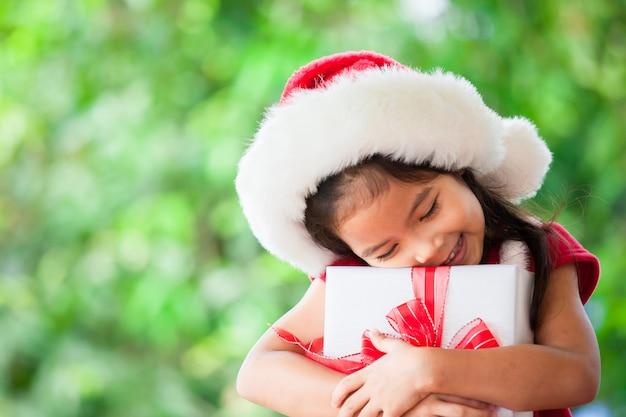 Nettes asiatisches kindermädchen in rotem hut sankt, der in der hand weihnachtsgeschenk hält