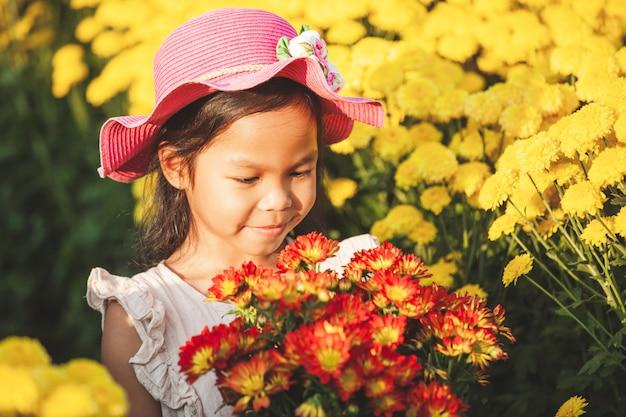 Nettes asiatisches kindermädchen lieben blume und hat spaß mit schöner blume im blumengarten