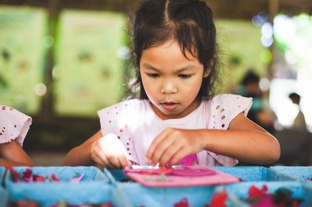 Nettes asiatisches kindermädchen machen ein handwerk mit recyclingpapier vom hacken der elefanten Premium Fotos