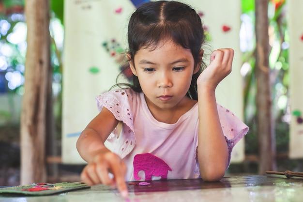 Nettes asiatisches kindermädchen machen ein handwerk mit recyclingpapier vom hacken der elefanten