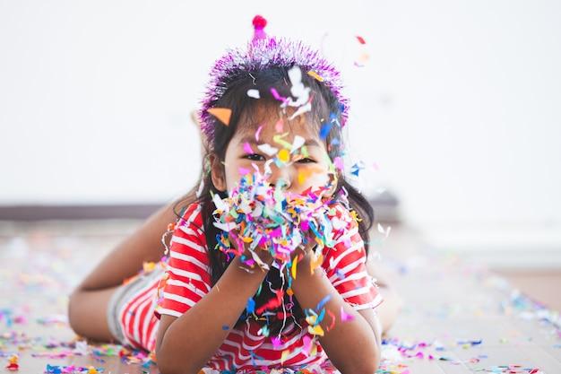 Nettes asiatisches kindermädchen mit den bunten konfettis, zum in ihrer party zu feiern