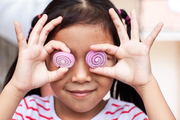 Nettes asiatisches kindermädchen mit geleesüßigkeiten lächelnd und ein lustiges gesicht machend