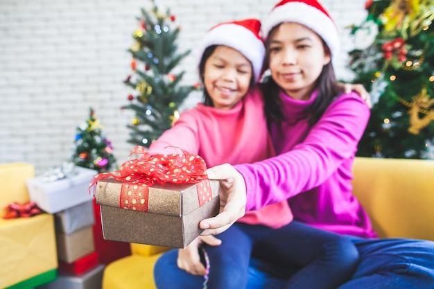 Nettes asiatisches kindermädchen mit ihrer mutter, die schöne geschenkbox hält und in der weihnachtsfeier gibt