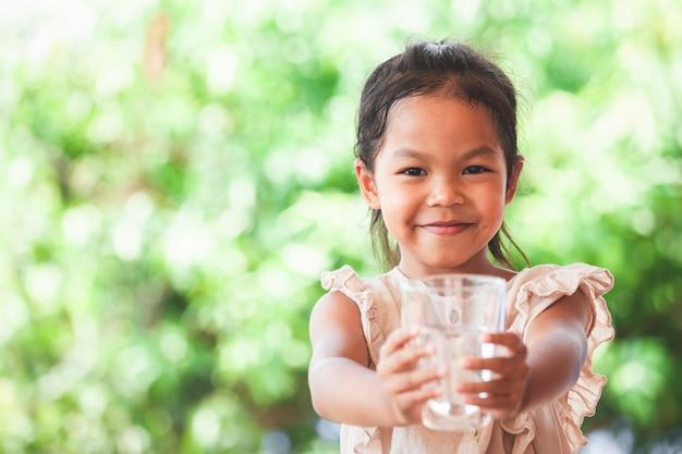 Nettes asiatisches kindermädchen mögen wasser trinken und glas süßwasser halten