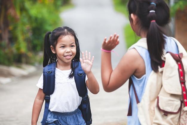 Nettes asiatisches kindermädchen und ihre ältere schwester, die hallo geste fünf machen, gehen vorher zur schule
