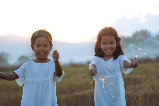 Nettes asiatisches kindermädchen zwei spielen mit feuerwunderkerzen auf dem festival in der reisfeld