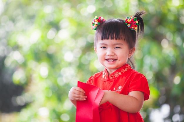 Nettes asiatisches kleines kindermädchen, das geld im roten umschlag lächelt und erhält