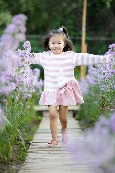 Nettes asiatisches kleines kindermädchen, das im garten mit spaß läuft und mit schöner natur im blumengarten genießt.
