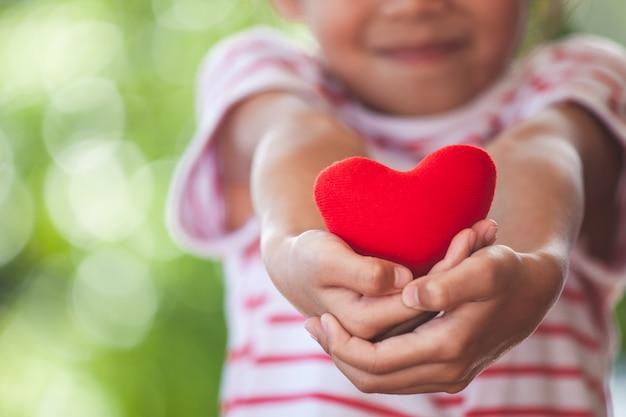 Nettes asiatisches kleines kindermädchen, das in der hand rotes herz mit sorgfalt und liebe zeigt und hält