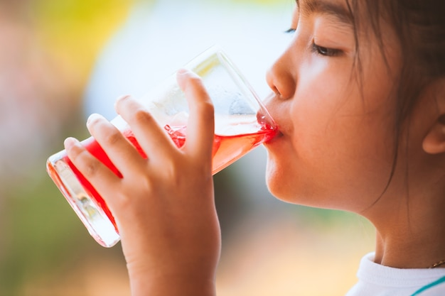 Nettes asiatisches kleines kindermädchen, das rotes saftwasser mit eis vom glas trinkt