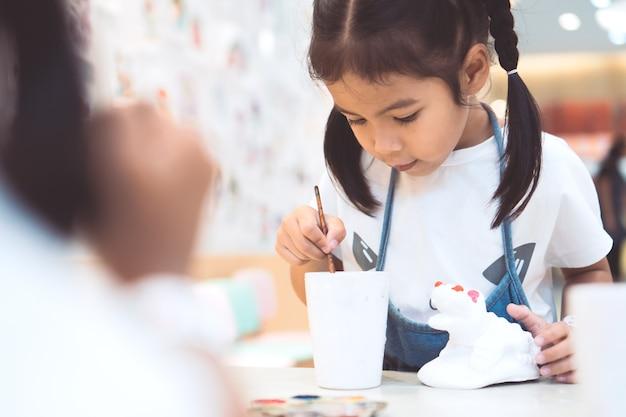 Nettes asiatisches kleines kindermädchen, das spaß hat, auf stuckpuppe zu malen