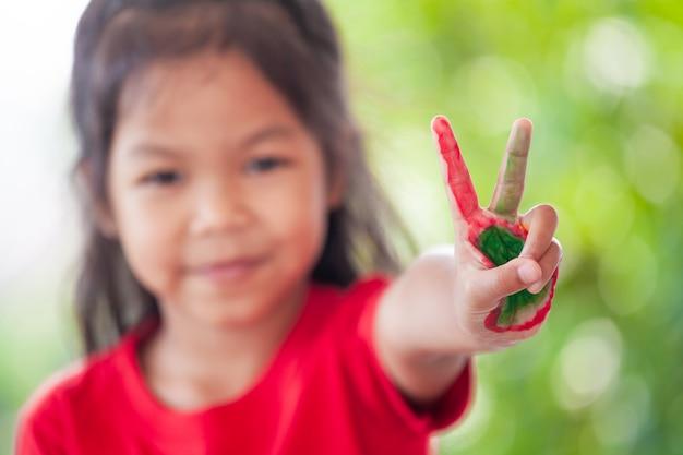 Nettes asiatisches kleines kindermädchen mit den gemalten händen, die finger nummer zwei zeigen