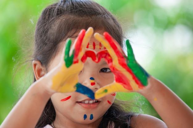 Nettes asiatisches kleines kindermädchen mit den gemalten händen machen die herzform, die mit spaß und lov bunt ist