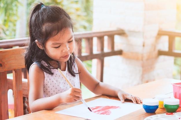 Nettes asiatisches kleines kindermädchenzeichnen und malte ein herz für die karte des valentinsgrußes mit spaß und glück