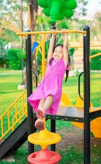 Nettes asiatisches kleines mädchen, das an einer horizontalen stange beim spielen im spielplatz hängt