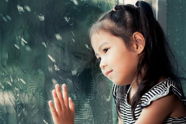 Nettes asiatisches kleines mädchen, das draußen durch das fenster am regnerischen tag schaut