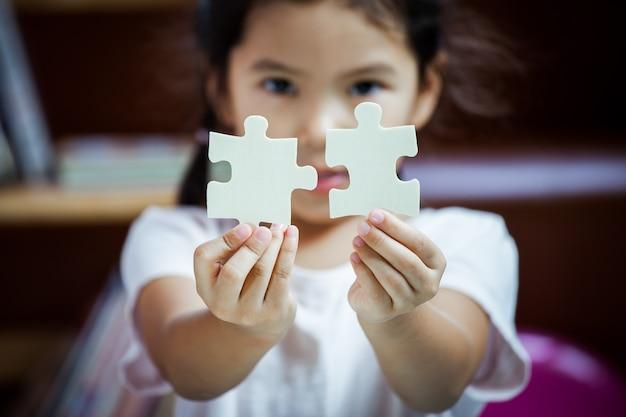 Nettes asiatisches kleines mädchen, das ein puzzlespiel macht