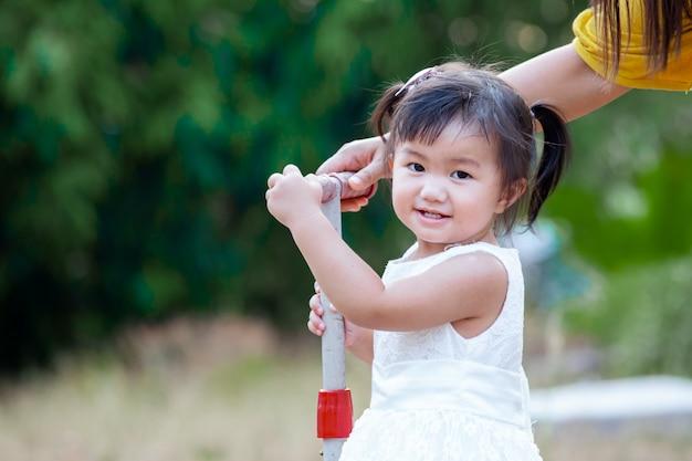 Nettes asiatisches kleines mädchen, das im park mit spaß und glück lächelt und spielt