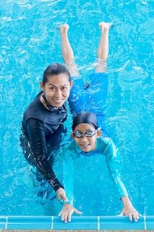 Nettes asiatisches kleines mädchen, das lernt, mit trainer in der freizeitmitte zu schwimmen