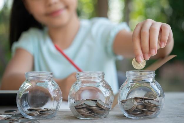 Nettes asiatisches kleines mädchen, das mit münzen spielt und geldstapel macht, kind spart geld in sparschwein, in glas. kind, das seine geretteten münzen zählt, kinder, die über das zukünftige konzept lernen.