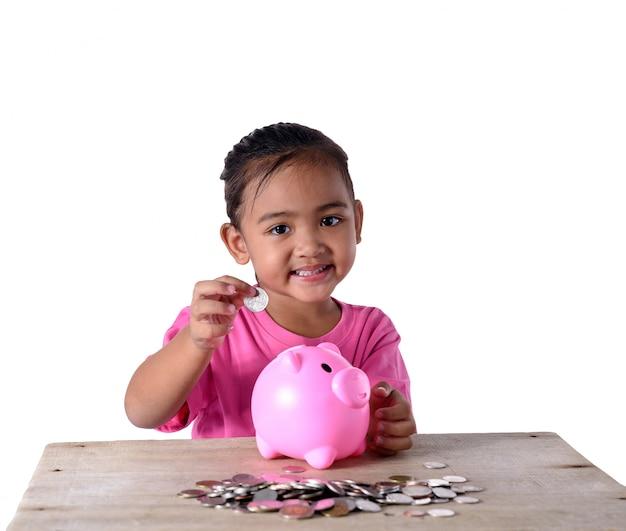 Nettes asiatisches kleines mädchen, das münzen in das sparschwein lokalisiert auf weißem hintergrund steckt