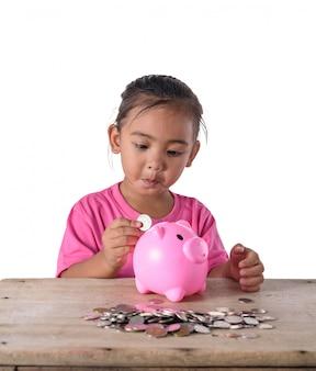 Nettes asiatisches kleines mädchen, das münzen in sparschwein steckt