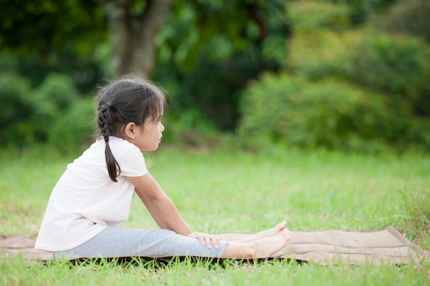 Nettes asiatisches kleines mädchen, das übung im park tut