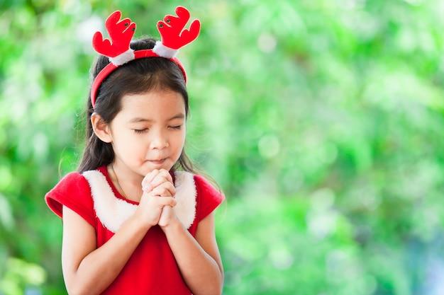 Nettes asiatisches kleines mädchen im weihnachtskleid schloss ihre augen und faltete ihre hand im gebet