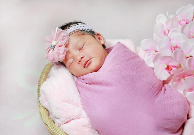 Nettes asiatisches kleines neugeborenes baby, das auf flauschigem weichem handtuch im korb schläft