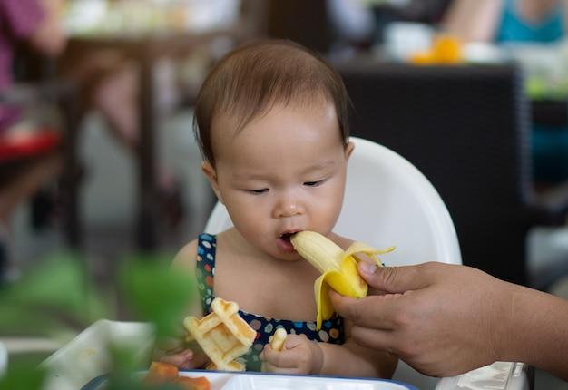 Nettes asiatisches kleinkindbaby, das banane isst