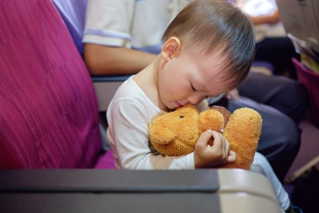 Nettes asiatisches kleinkindjungenkind, das liebevollen & küssenden teddybär ausgestopften spielzeugfreund während des fluges im flugzeug umarmt