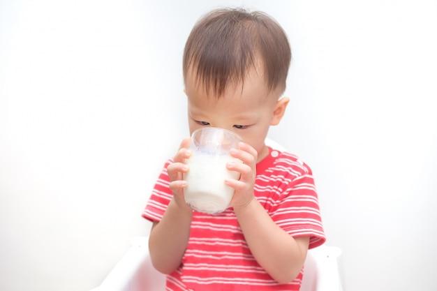 Nettes asiatisches kleinkindjungenkind, das milch von einem glas trinkt