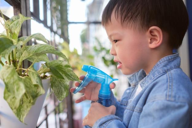Nettes asiatisches kleinkindjungenkind, das spaß unter verwendung der sprühflasche wässert goldene pothos hat
