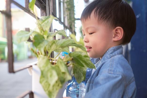 Nettes asiatisches kleinkindjungenkind, das spaß unter verwendung des sprühflaschenwassers hat