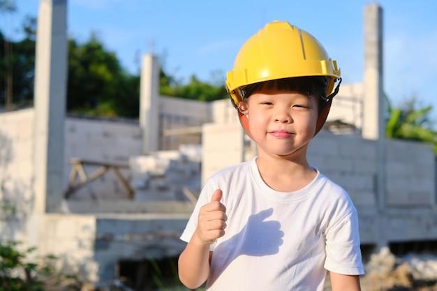 Nettes asiatisches lächelndes glückliches kindergartenkind, das gelben bauhelm oder sicherheitsschutzhelm trägt