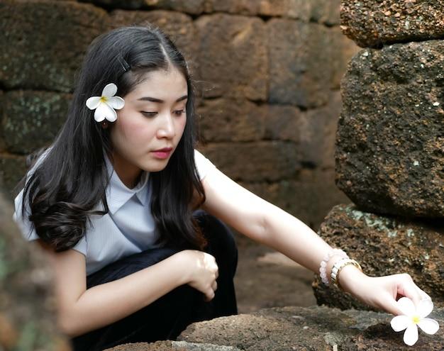 Nettes asiatisches mädchen auf naturreise im freien. sie lächelt und posiert in vielen augenblicken mit blumen.