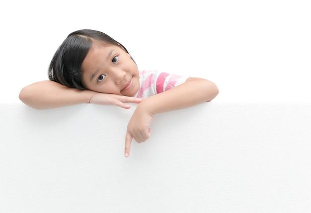 Nettes asiatisches mädchen, das auf das weiße fahnenbrett lokalisiert auf weißem hintergrund mit kopienraum für inpu zeigt