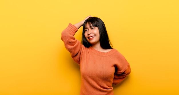 Nettes asiatisches mädchen, das auf gelbem hintergrund lächelt. leere, junge frau. platz für werbung. platz kopieren