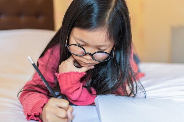 Nettes asiatisches mädchen, das denkt, notizen auf dem bett schreibend